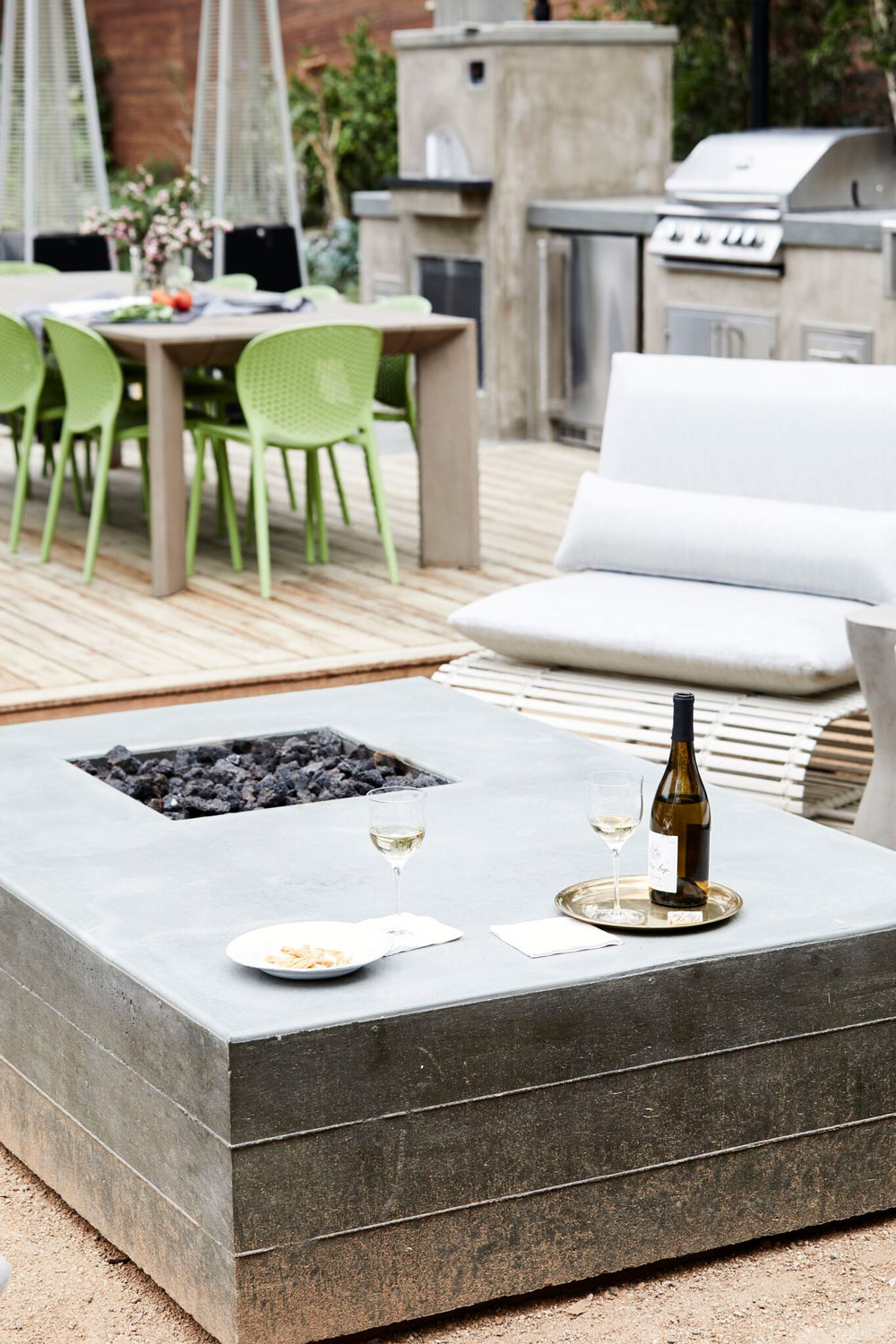 A generous outdoor fireplace with oversized lounge chairs becomes the perfect spot to keep warm on cool evenings.