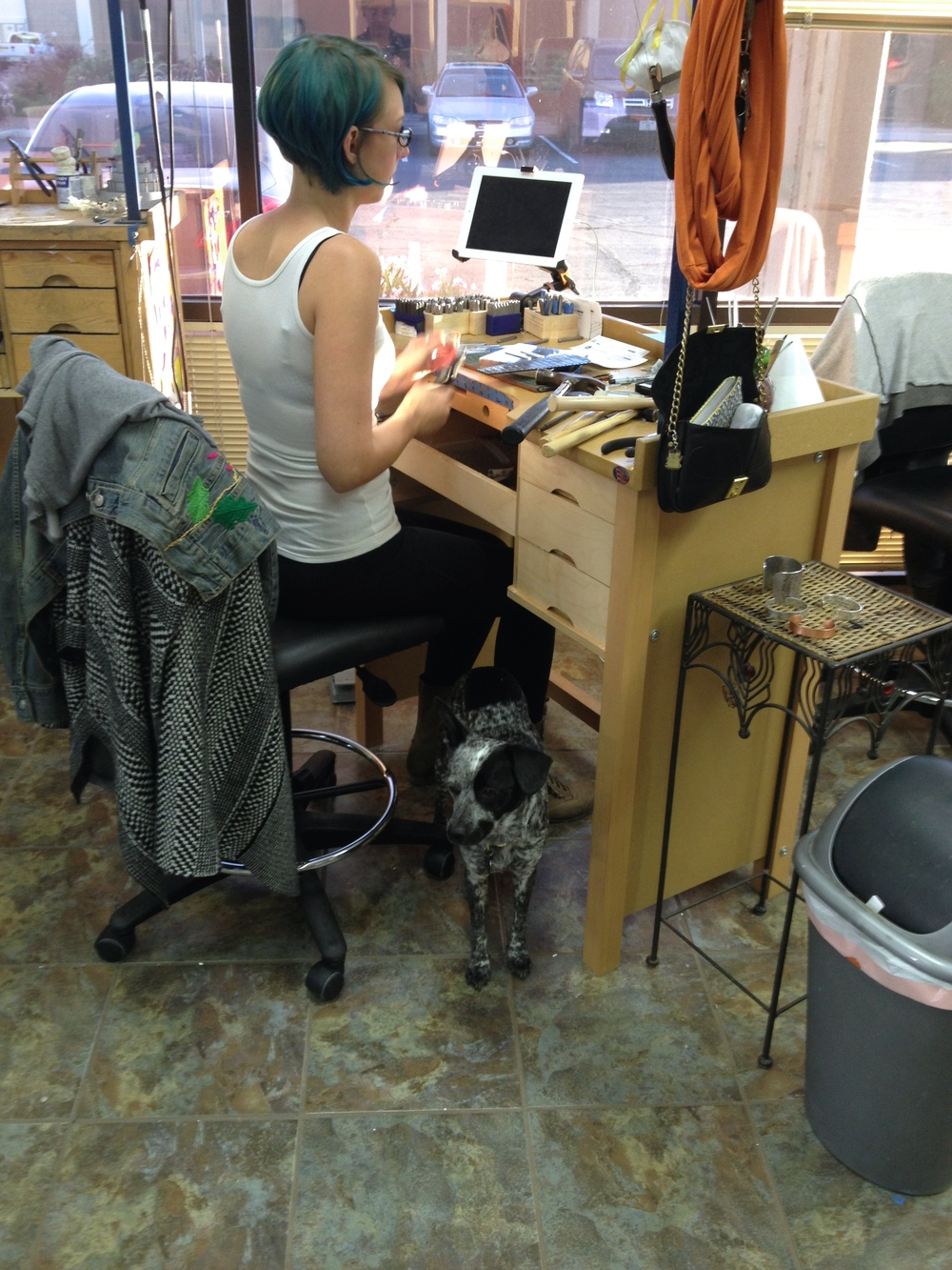 cassie at her work bench, a moondog at her feet.