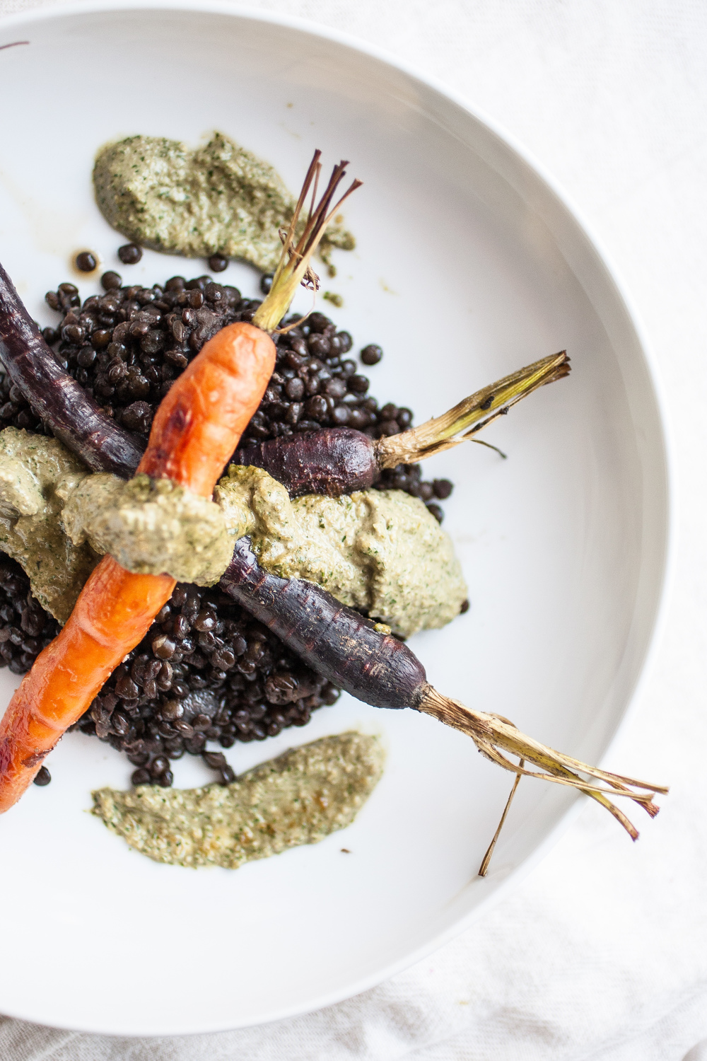 Produce On Parade - Roasted Carrots & Beluga Lentils with Carrot Greens Pesto - Roasted carrots rest atop beluga lentils, dressed with a fresh, carrot greens pesto. This exquisite dish is done in under an hour and will definitely impress.