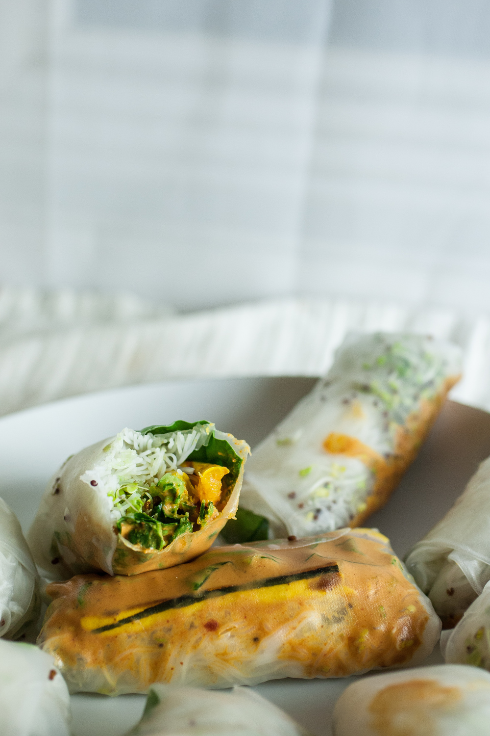 Produce On Parade - Delicata Spring Rolls - The peel of a delicata squash is perfectly edible and tender, which makes them a perfect partner in these fresh rolls, nestled between avocado, rice noodles, and chard. Dip them in my creamy red curry sauce.