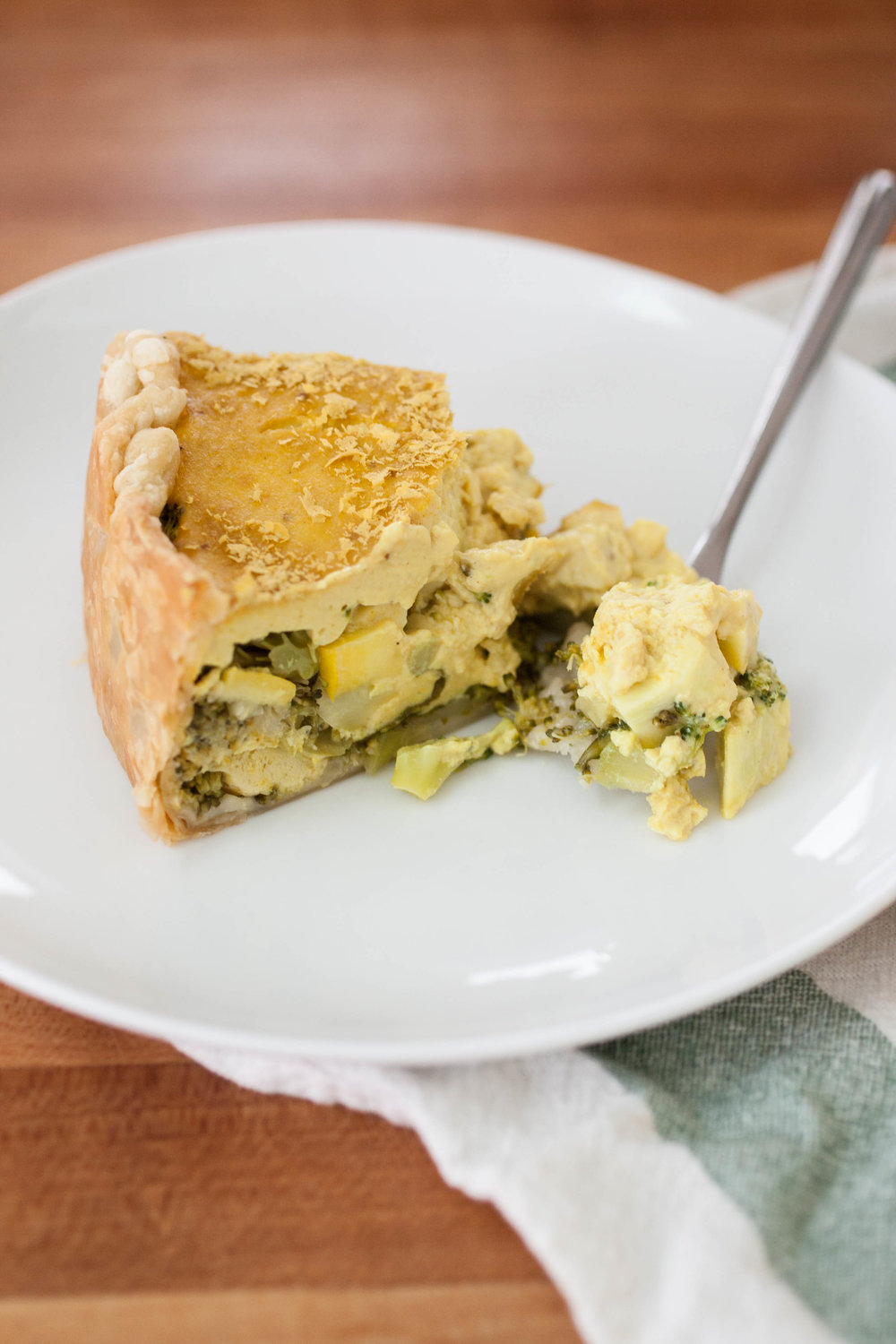 Produce On Parade - Broccoli & Squash Quiche - Flaky puff pastry envelops a fluffy, cheesy, vegan quiche that's loaded with nutritious broccoli, squash, and spinach. Kala namak salt gives this savory dish that eggy quality and tofu provides healthy protein. It's a super easy meal that's perfect for breakfast or dinner.