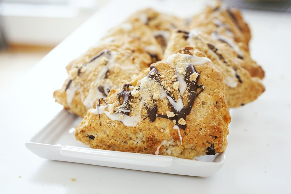 Produce On Parade - S'mores Scones - Seriously delicious and fun, these s'mores scones are a wonderful treat for the youngins and those who are young at heart. Studded with chocolate chunks and bits of graham cracker, they are drizzled with chocolate as well as a marshmallow glaze then topped with crushed graham cracker. These are incredibly easy to make and done in a flash; so be the hit of the bonfire or party with my s'mores scones!