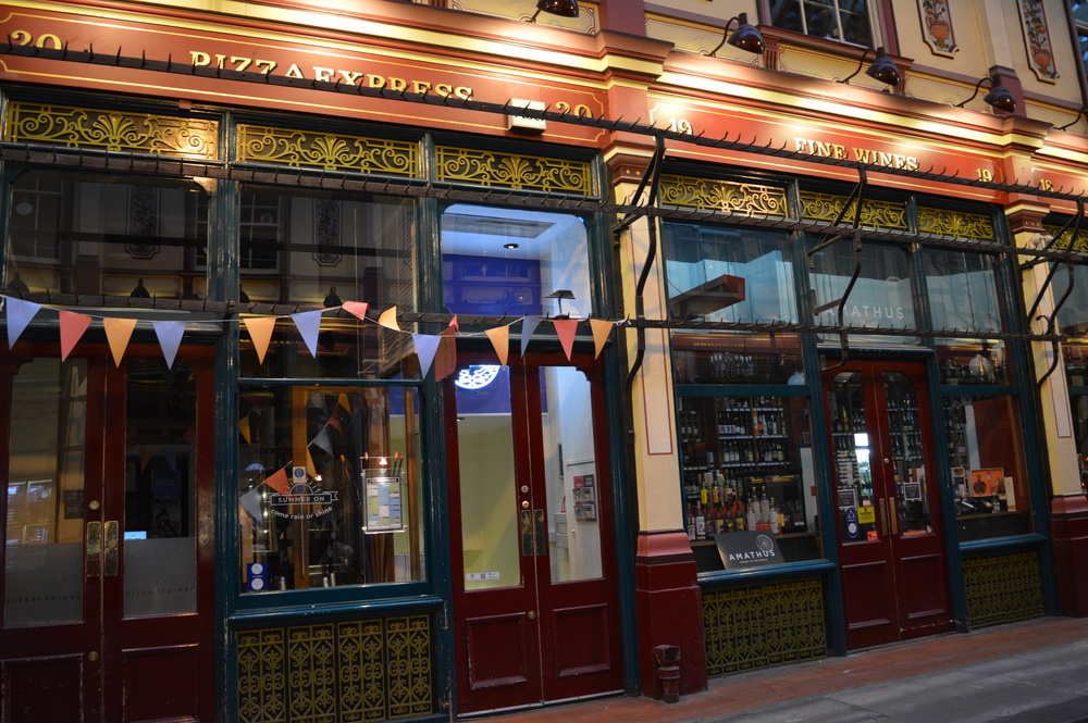 Leadenhall Market may be full of modern shops and restaurants now, but the hooks in front of the old butcher's shops used for hanging carcasses remain - used here by Pizza Express for their bunting.  How times change.