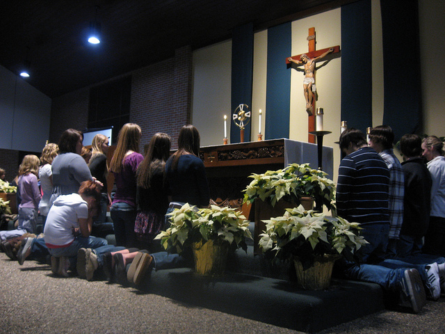 Teens gather for Adoration during one of their retreats. The parish offers opportunities for Adoration on Tuesdays in the chapel.