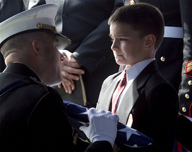 Eight-year-old Christian Golczynski accepts the flag for his father, Marine Staff Sgt. Marc Golczynski, during a memorial service. Marc Golczynski was shot during his second tour in Iraq just a few weeks before returning back home.     Learn more about Christian and his life since this iconic photograph here.