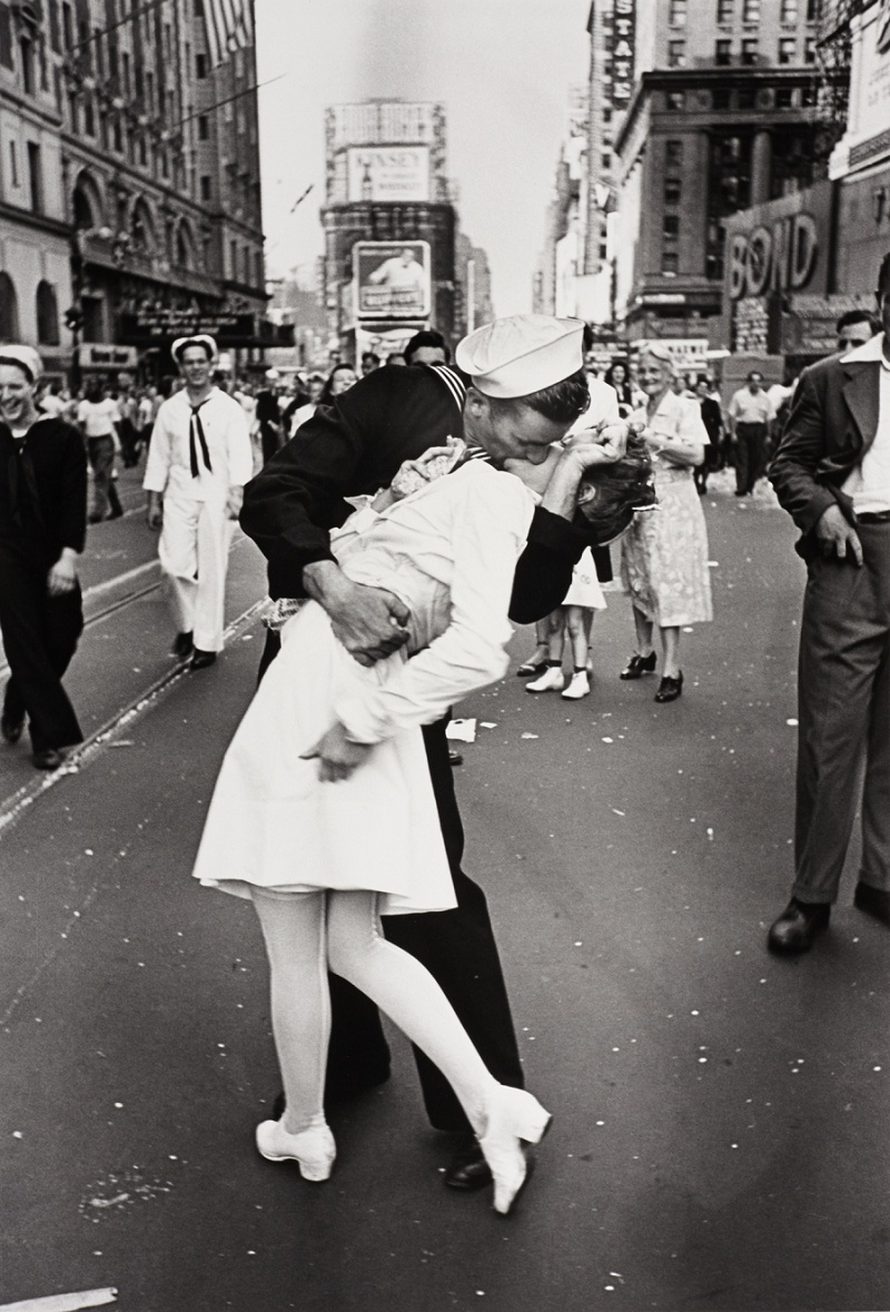 Victory Over Japan  (V-J) Day in Times Square , a photograph by Alfred Eisenstaedt, was published in  Life  in 1945 with the caption,   In New York's Times Square a white-clad girl clutches her purse and skirt as an uninhibited sailor plants his lips squarely on hers.    Read the story behind this infamous and most copied photograph here.