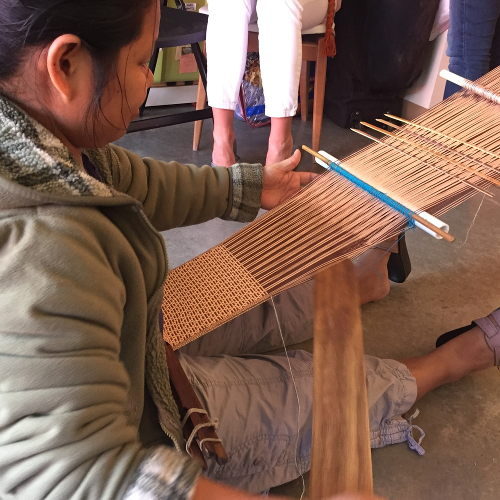 Mu Mu using the back strap loom that her grandmother taught her how to use when she was 10 years old in Burma.