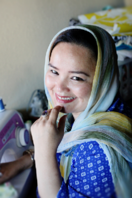 Khatera at her sewing desk in her home where she works. (Photo credit to Jane Marie Photography)