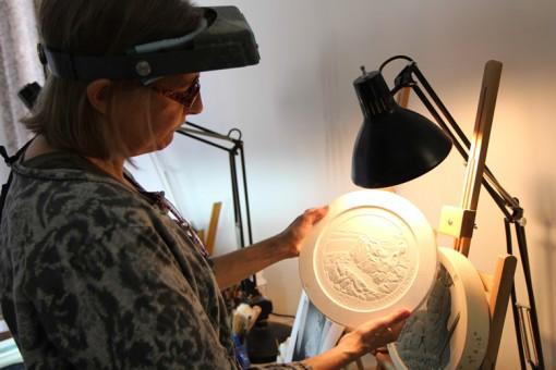 Artista de la casa de mondeda EE.UU ,Phebe Hemphill, Medallic Escultor. Febe esta graduada en la Academia de Pensilvania de Bellas Artes; también trabajó como escultor en Franklin Mint durante 15 años. Aquí, Febe inspecciona un modelo de yeso.