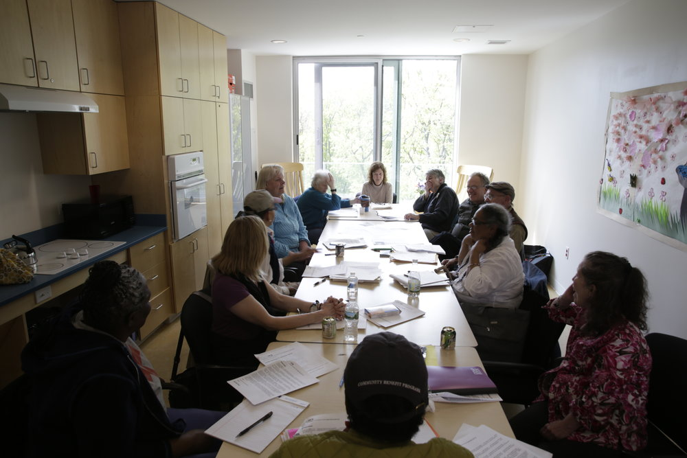 Courtesy Photo | Members listen attentively as one person reflects on the poetic idea of the day in a poetry workshop session in the kitchenette of Mount Pleasant Home in Jamaica Plain in spring, 2016. The nature scene outside the window is inspirational.