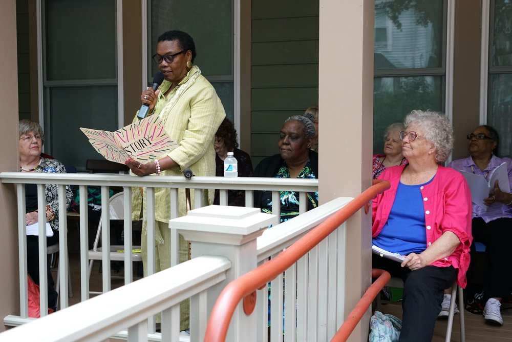 "Photo by Joni Lohr | Workshop poet Gloria Johnson reads her poems at Jamaica Plain Porchfest, as other members of ""Never Too Late to Be a Poet"" spring, 2016 workshop, who also read their poems before a crowd, look on. Workshop participants were invited to read and were taped by BNN-TV. Young people from local youth organizations also participated. More than 70 porches hosted music and other performances at JP Porchfest July 9, 2016."