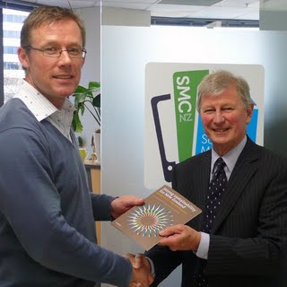 Nakedize managing director Simon Hertnon presents New Zealand National UNESCO Commission chairman Sir Brian Gould with the first copy of Strong Sustainability for New Zealand at the paper's launch at the Science Media Centre, Wellington, on 3 September 2010.