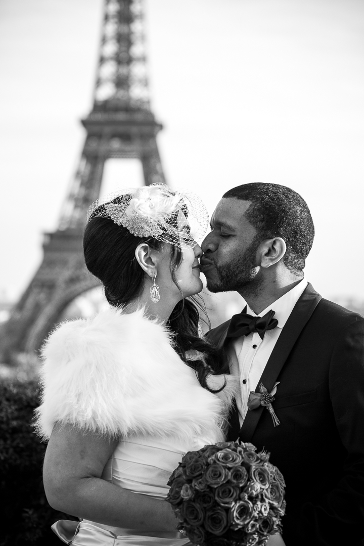 A bride and groom in black and white kiss in front of the Eiffel Tower, Paris. Destination wedding photography - Amy Stallard Photography