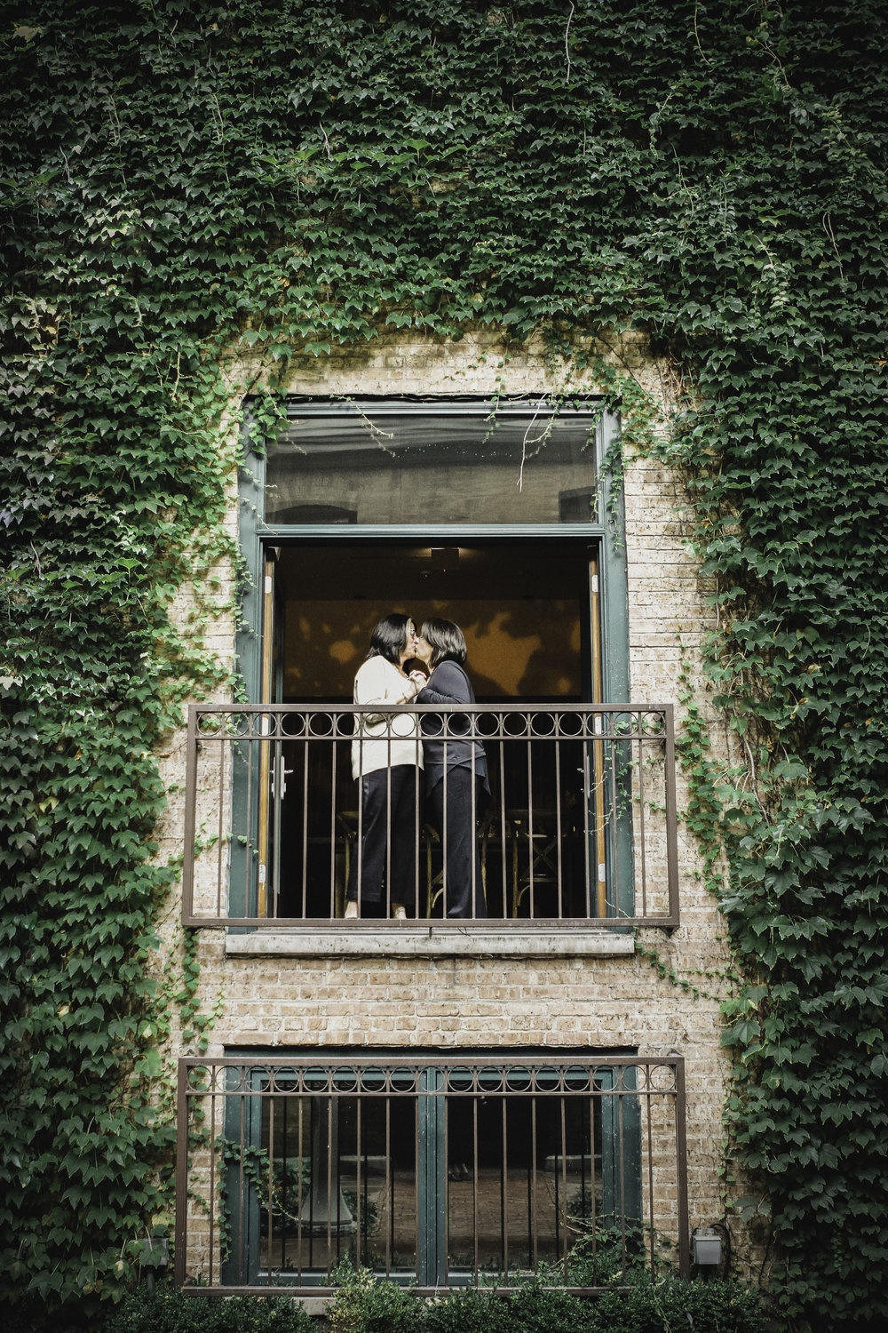 Two brides kiss at an informal wedding ceremony at Ivy Room (Tree Studios) Chicago Wedding Photography (c) Amy Stallard