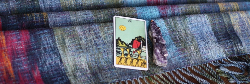 The Witch in the Woods: 8 of Cups and an amethyst rest on handwoven cloth