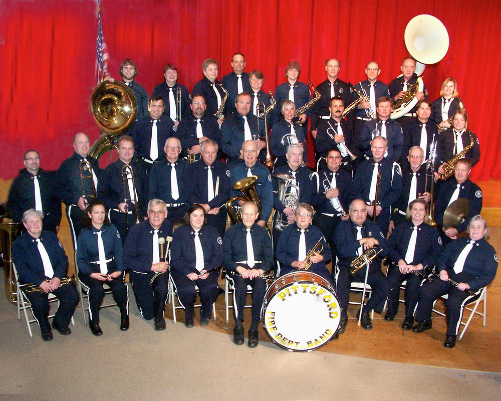 Carol Aldridge is sitting directly behind the bass drum, just to the left of Tedo. John Aldridge is in the second row, fourth person from the left, between Tom Thompson and Tom Powell.