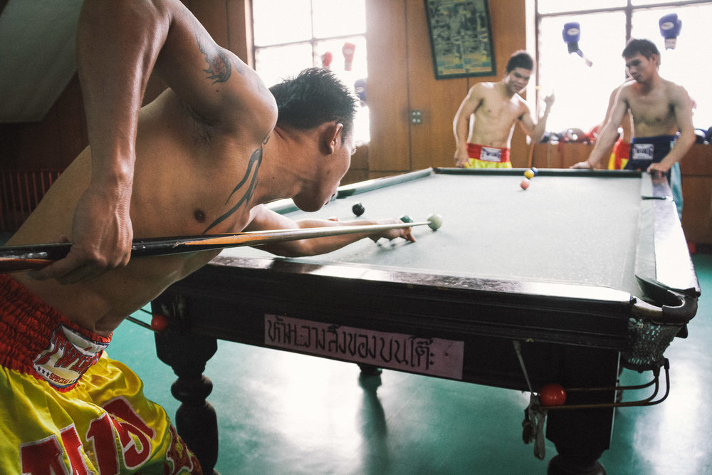 Muay Thai fighters in Bangkok, Thailand take a training break to play billiards. Photo by Daniel J. Powell