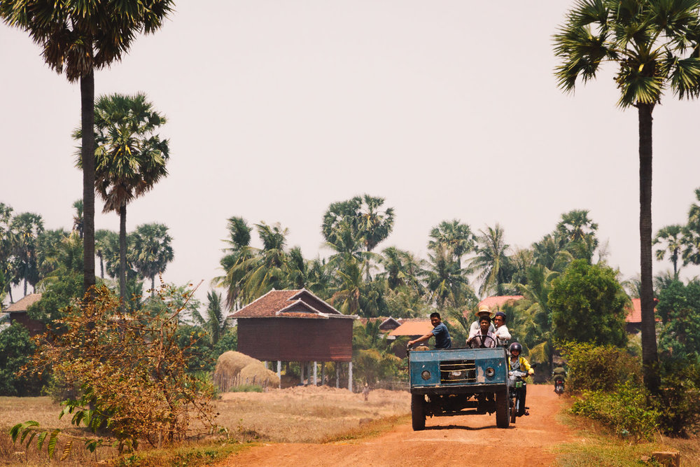 A farm truck travels down a dirt road in Siem Reap Province, Cambodia. Photo by Daniel J. Powell