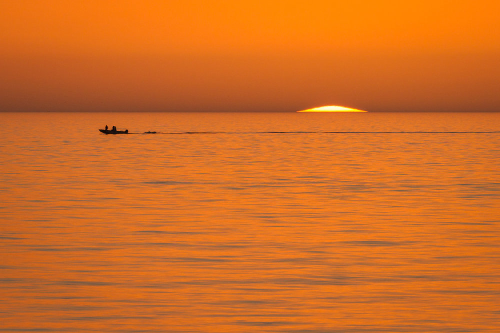 A boat passes while the last sliver of the sun sets into the ocean