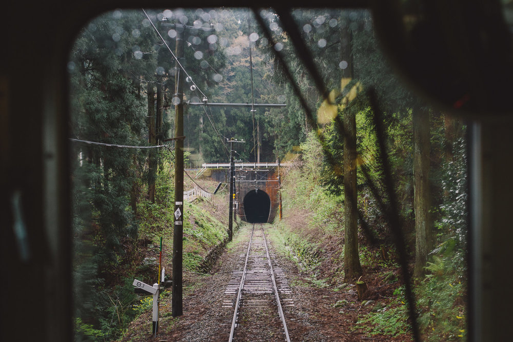 A train approaches a tunnel along the Japan's Toyama Chihō Railway Main Line