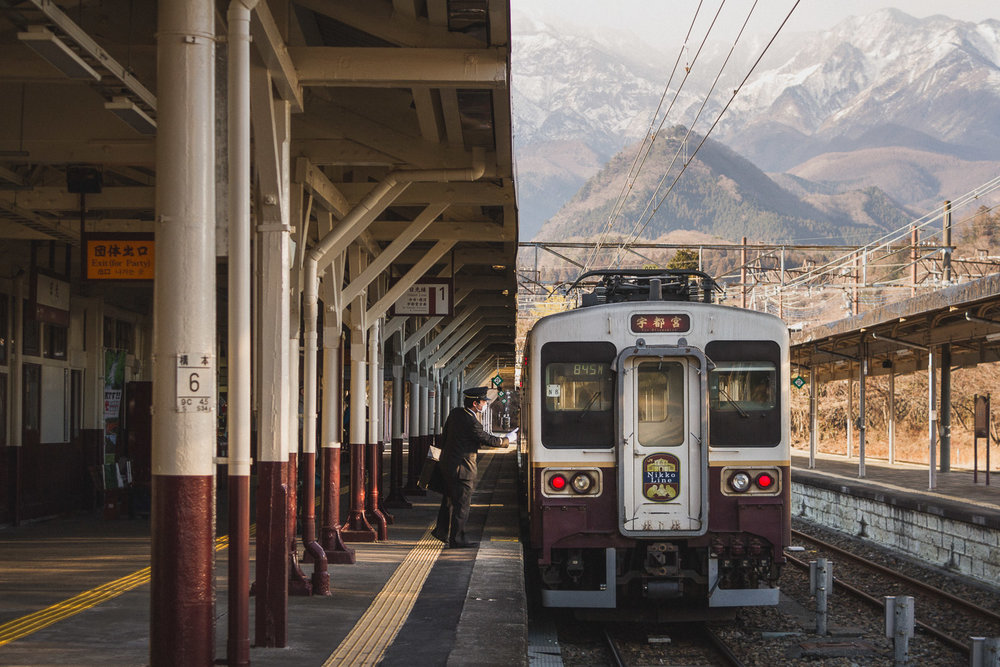 A train conductor and his train with a backdrop of mountains at JR Nikko Station, Japan. Photo by Daniel J. Powell