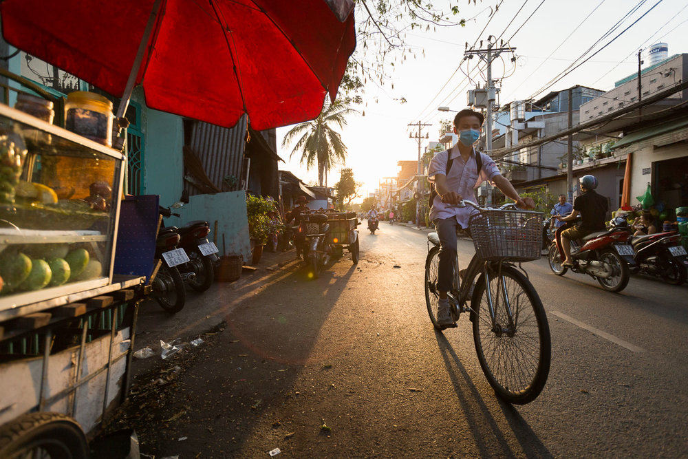 A man rides his bicycle at sunset in Ho Chi Minh City, Saigon, Vietnam