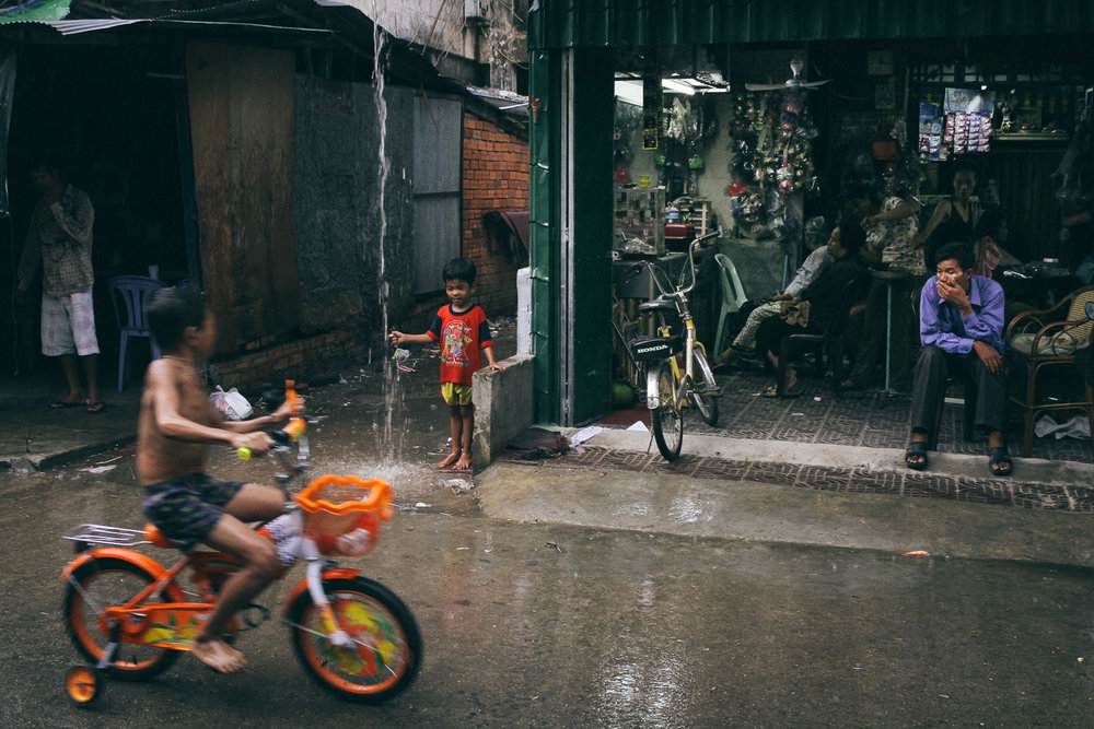 Children play in the rain on a street in Phnom Penh, Cambodia