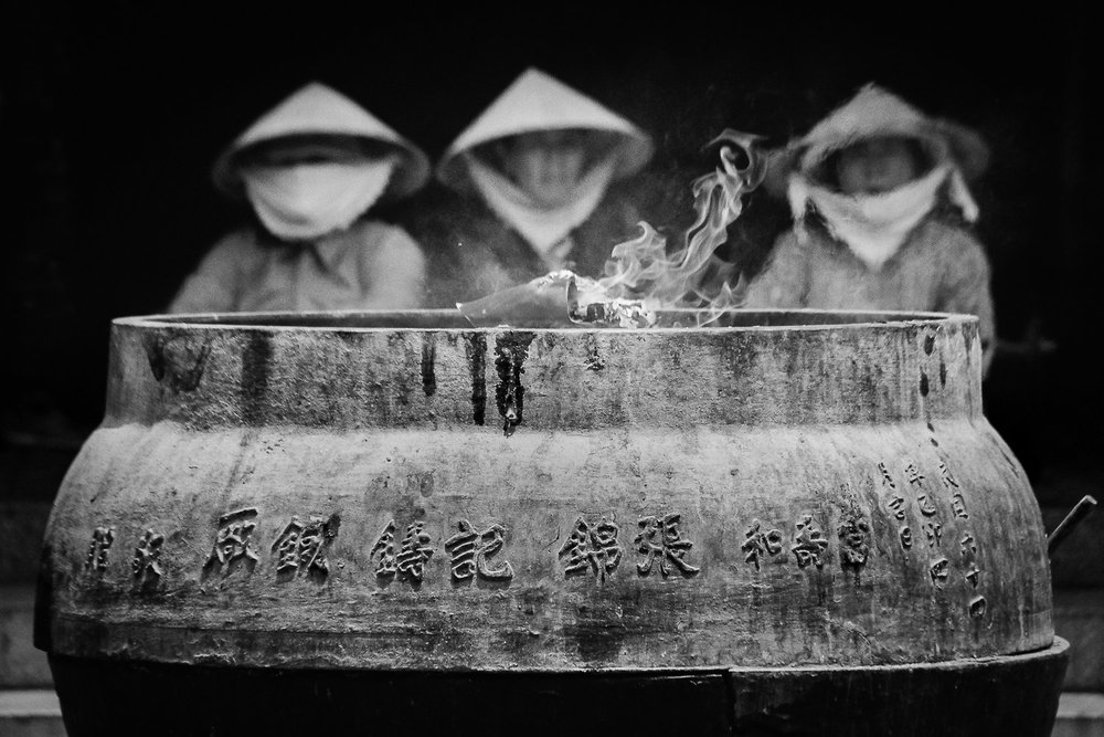 Three women tend a cauldron of burning prayer papers at Chua Xu Thanh Mieu (Lady Chua Xu Temple) in Vietnam's Mekong Delta region. Photo by Daniel J. Powell