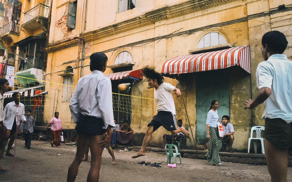 Men play takraw on a street in Yangon, Myanmar, Burma