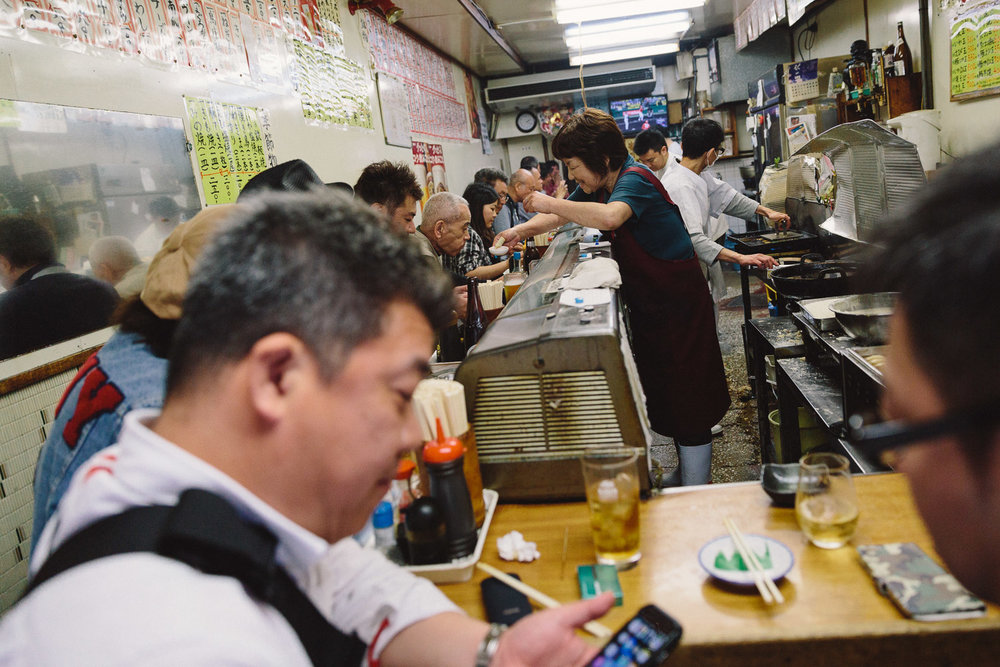 A local restaurant in Osaka, Japan serves customers food and drinks with a smile