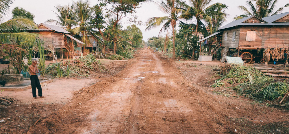 A man stands next to a road under construction in his village in Siem Reap Province, Cambodia