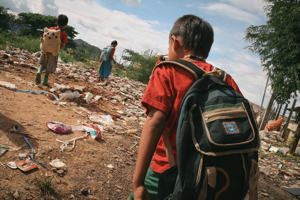 Migrant schoolchildren from Myanmar walk home through a trash dump near Mae Sot, Thailand. Photo by Daniel J. Powell