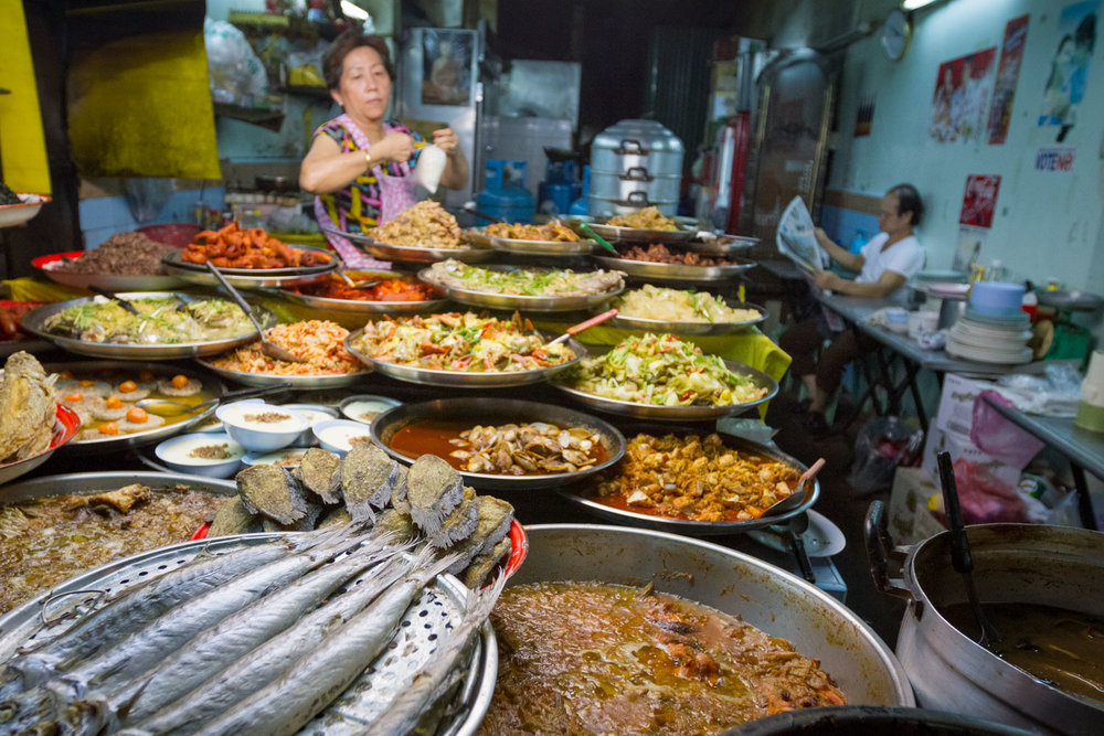 A woman tends to her restaurant's display of food in Bangkok, Thailand's Chinatown District while her husband reads the newspaper. Photo by Daniel J. Powell