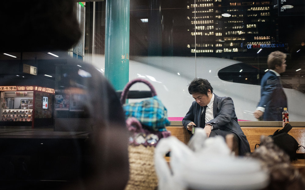 Salaryman in Japan walking past and waiting for the Shinkansen at Tokyo Station, Japan. Photo by Daniel J. Powell