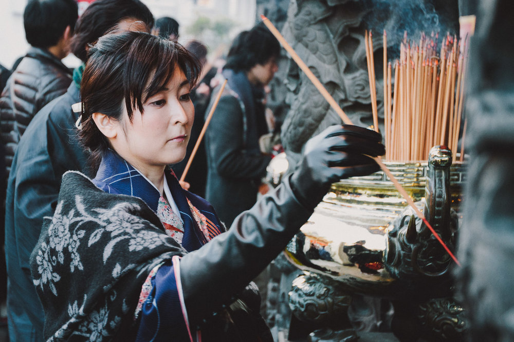 A woman offers incense during CHinese New Year at Yokohama Ma Zhu Miao temple, Japan. Photo by Daniel J. Powell
