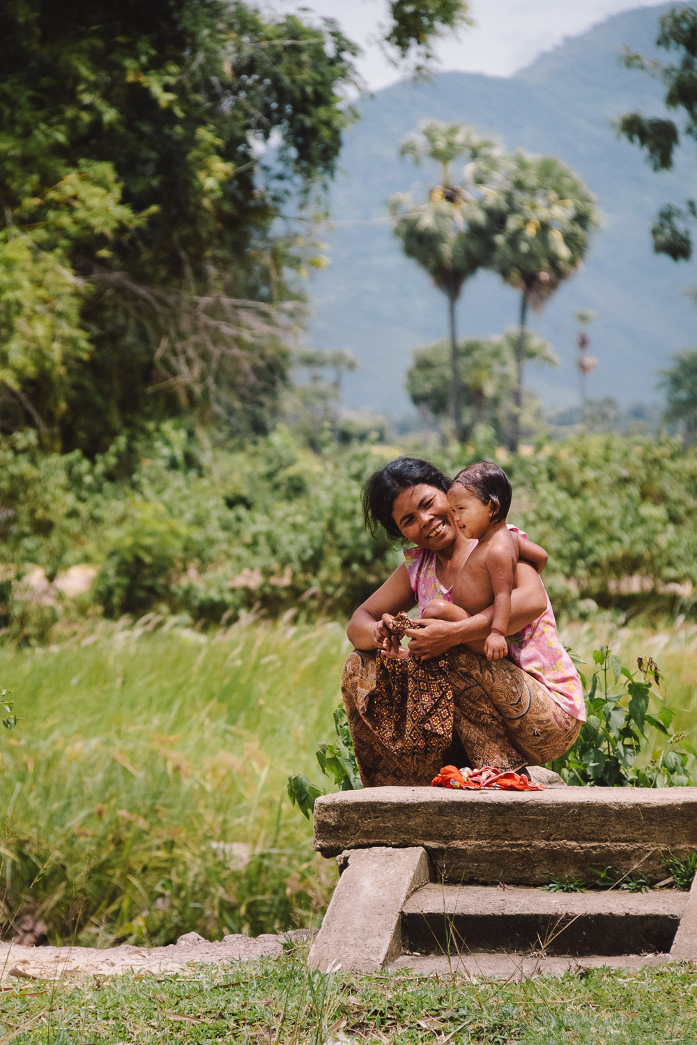 A grandmother smiles and holds her granddaughter after a bath in rural Cambodia. Photo by Daniel J. Powell