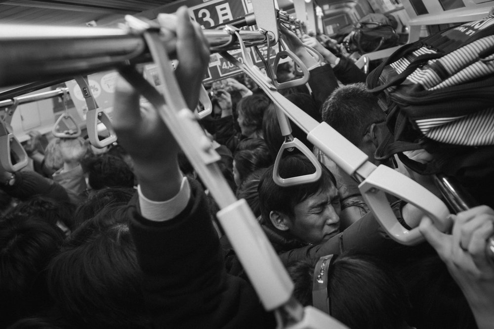 A man grimaces on a packed commuter train in Tokyo, Japan. Photo by Daniel J. Powell