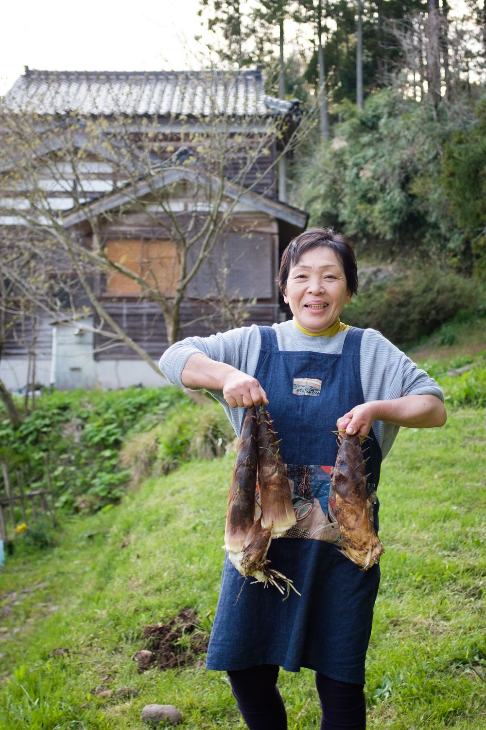 A woman holds freshly harvested bamboo shoots on Japan's Noto Peninsula, Ishikawa Prefecture