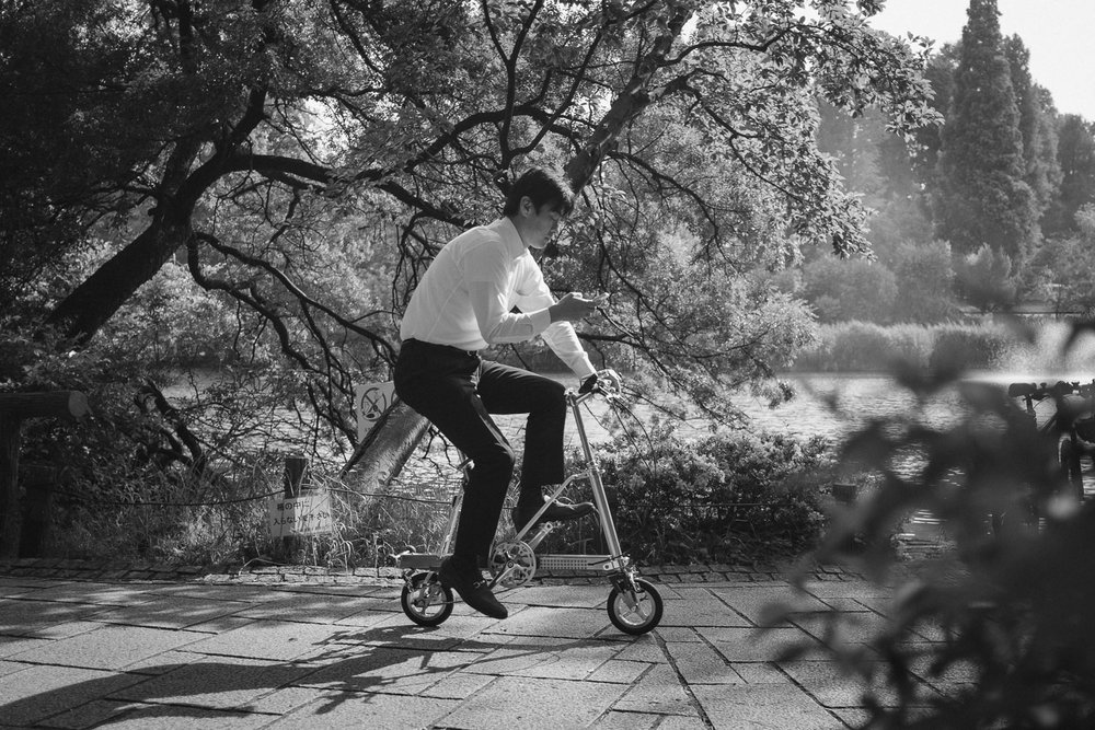 A salaryman reads his mobile phone while riding a fold-up bicycle through Inokashira Park in Tokyo