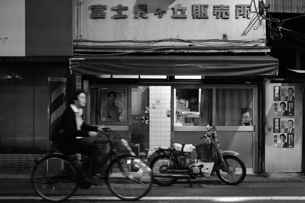 A salaryman bicycyles home at night past an old bottled milk distributor in Tokyo, Japan