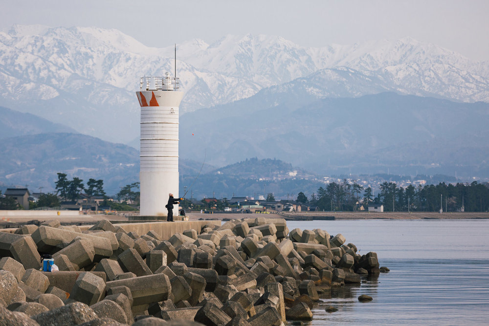 A fisherman casts his line near Kurobe, Toyama, Japan with the Japanese Alps in the background