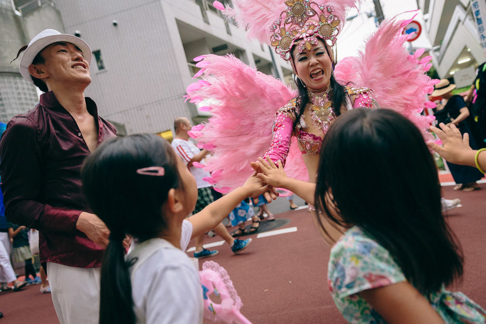 A female dancer greets young Japanese girls during the annual Fujimigaoka Samba Festival in Tokyo, Japan
