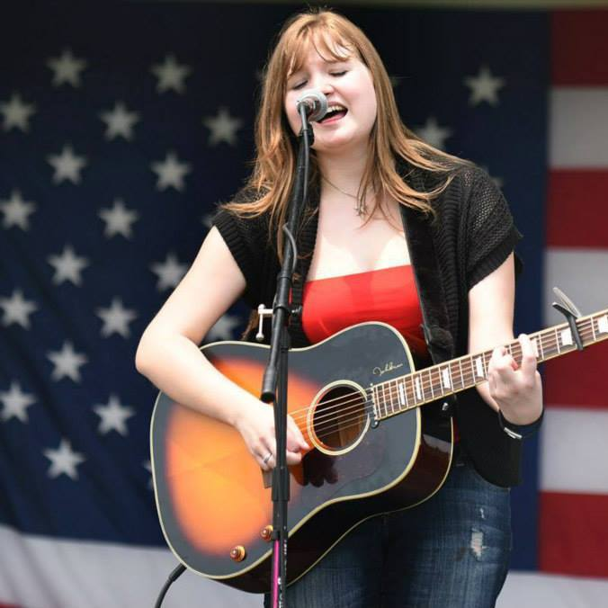 Laura Stoecker/lstoecker@dailyherald.com Jenn Panfil, 22, of Glen Ellyn performs at Bartlett's 22nd annual Fourth of July festival on Friday. Self taught in the guitar, Panfil has been playing since she was 16 and has recently put out her first album. She frequently performs in the Glen Ellyn and Lombard area. This is her first time performing at the festival.