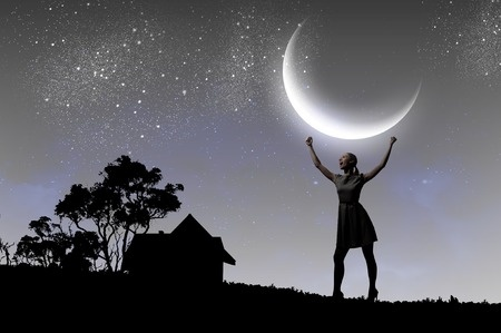 woman holding up crescent moon