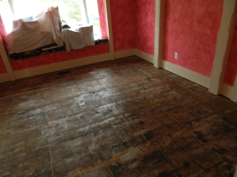 BEFORE, THE FLOOR AFTER THE PARQUET WAS REMOVED. THE REMAINING GLUE AND  ASPHALT PAPER