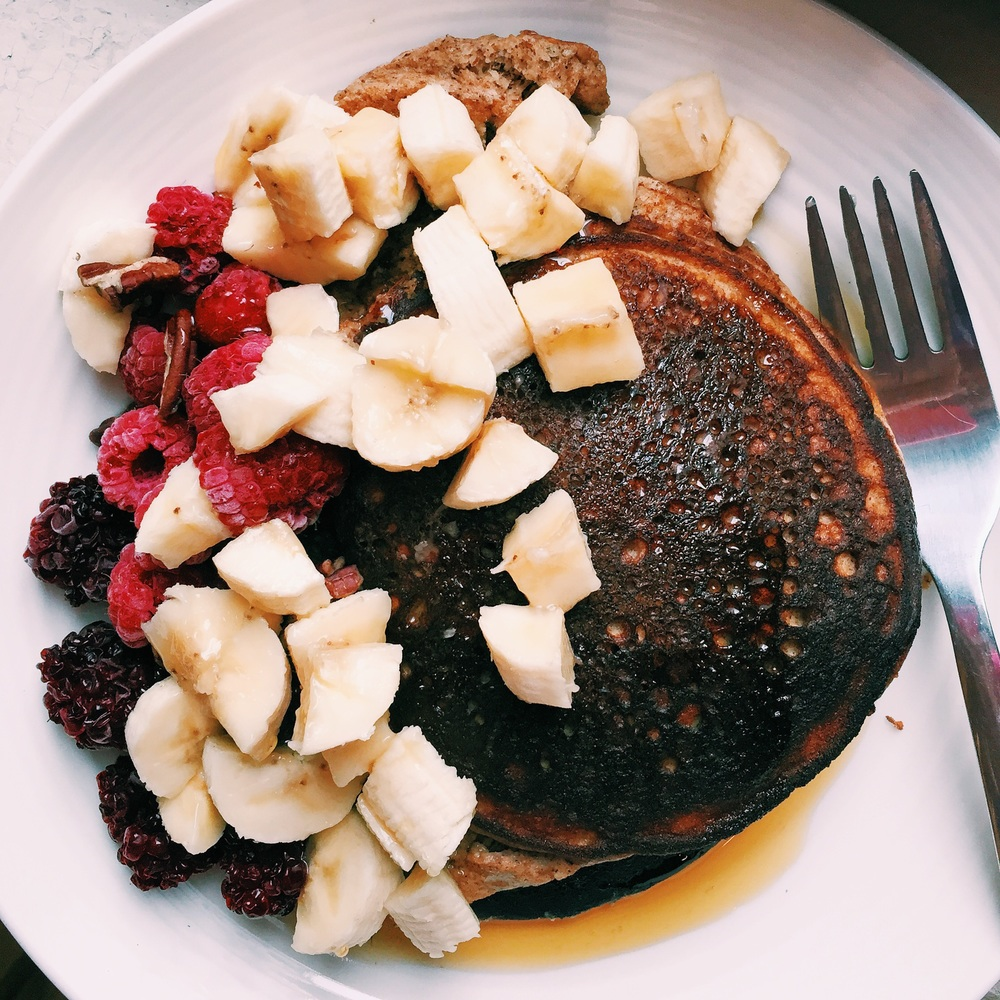 Smothering burnt paleo pancakes with three different kinds of fruit and maple syrup to make them look and taste more appealing. It kind of worked.