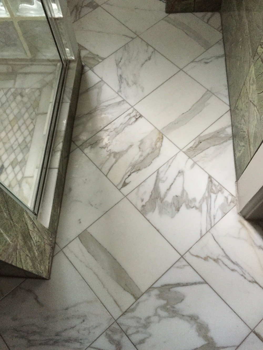 This Calacatta Marble powder room floor was  dull and etched then brought to a shine with a wet polishing system.