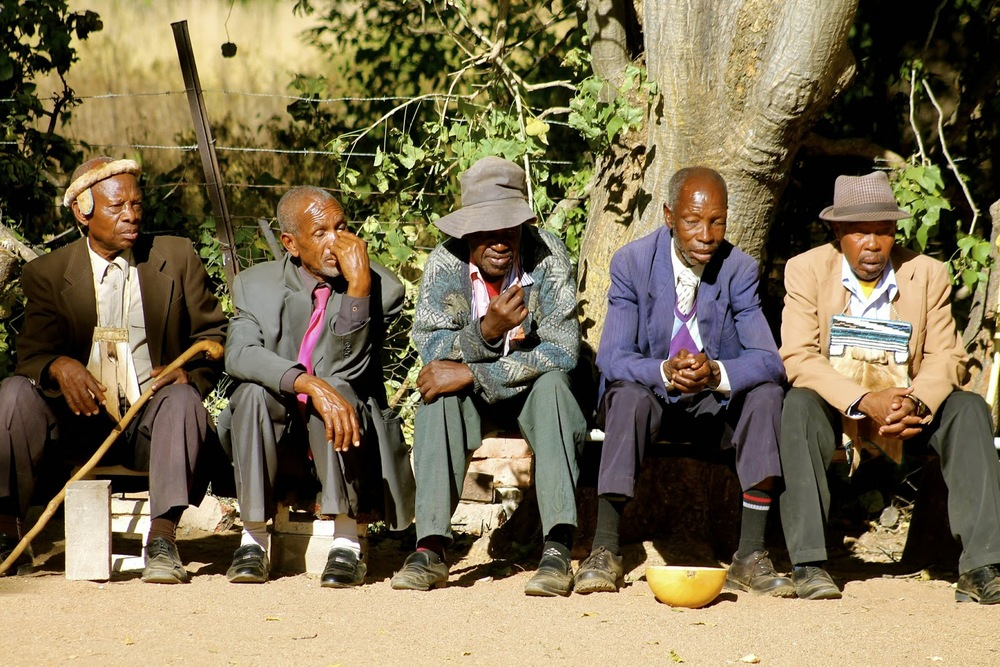 Sometimes I think of this picture with the name  A Gathering of Old Men . It's a pretty typical sight in rural South Africa, seeing men sitting in a line, chatting and avoiding the sun.