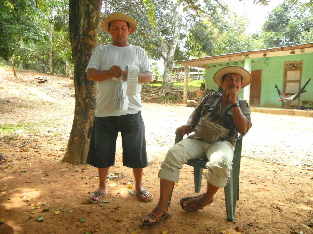 Lottery vendor Euclides takes a break from his trek while Digi peruses the numbers.