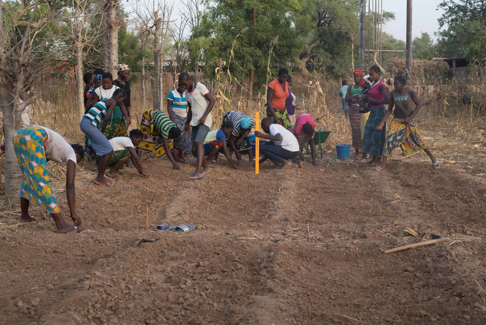 The girls work with one of our partners to create larger garden beds for replanting.